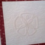Custom quilting on the sand dollar block of a candlewick quilt